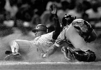 Milwaukee's Darryl Hamilton (left) created a cloud of dust as he slides past Baltimore catcher Bob Melvin to score on B.J. Surhoff's third-inning single Friday night.  The run gave the Brewers a 4-3 lead, and they went on to beat the Orioles in the opener of the three game series at County Stadium, 8-5.