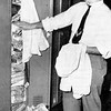 "APRIL 1954- Neal Russo of the sports staff, frustrated by the lack of space in which to cache another shirt, reconsiders his annual resolution to clean out his seven-year accumulation of ""valuables"" from locker which compares favorably with the booby trap closet of Fibber McGee of radio fame"