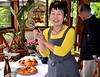 Aunt Hiroko (same birthday/date as me) showing off pizza slicer I gave her --- preparing for lunch in sunroom;  Uncle Akinami in the background.
