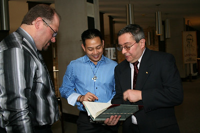 Br. Duane Lemke, Fr. Joseph Dinh and Br. Frank Presto look at the monastery record book; the book contains information about each event of significance at Sacred Heart Monastery.