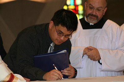 Frater Joseph Vu, SCJ, signs his statement of vows; Fr. Charlie Bisgrove looks on.