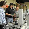John Cross<br /> South Central College mechatronics instructor Doug Laven (center) and students Jacob Wojszynski (left) and Ryan Kontak sand before a production floor simulator.