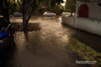 March 20. Wet Feet A downpour turns this street and footpath into a fast flowing stream.