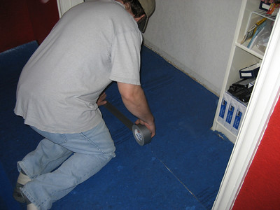Using duct tape to attach the underlayment in the closet.