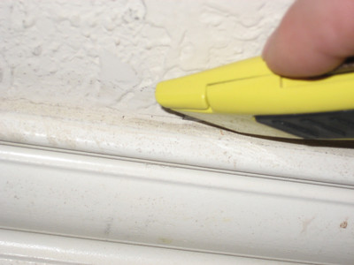 Using utility knife to break caulk seal before removing baseboard.
