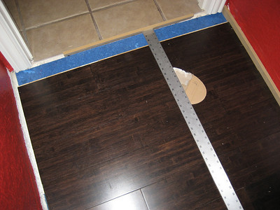 Measuring for final row of flooring in doorway.