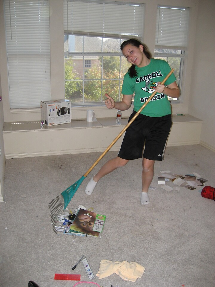 Alli raking the carpet to make it easier to pick up the junk.