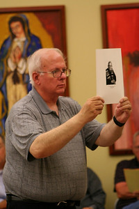 Fr. Joe Dean holds a photo of Fr. Howard Melzer as he is remembered during the memorial service.