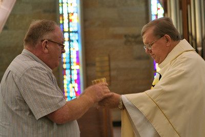 Dn. David Nagel receives the cup from Fr. Bill Pitcavage.