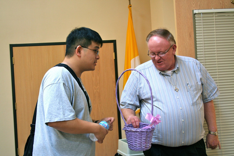 A basket leftover from Easter decorations was used for distributing table numbers.  Novice Joseph Vu picks his number from Dn. David Nagel.