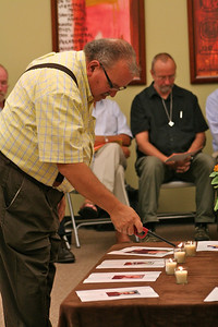 Fr. Yvon Sheehy lights a candle to remember a deceased SCJ.