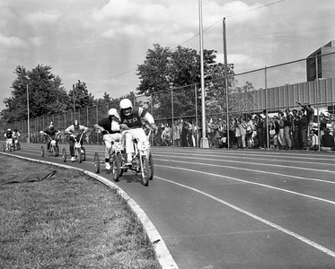 trike - Students compete in the Trike Derby on the athletics practice field and track, now Marks Field during Homecoming 1968