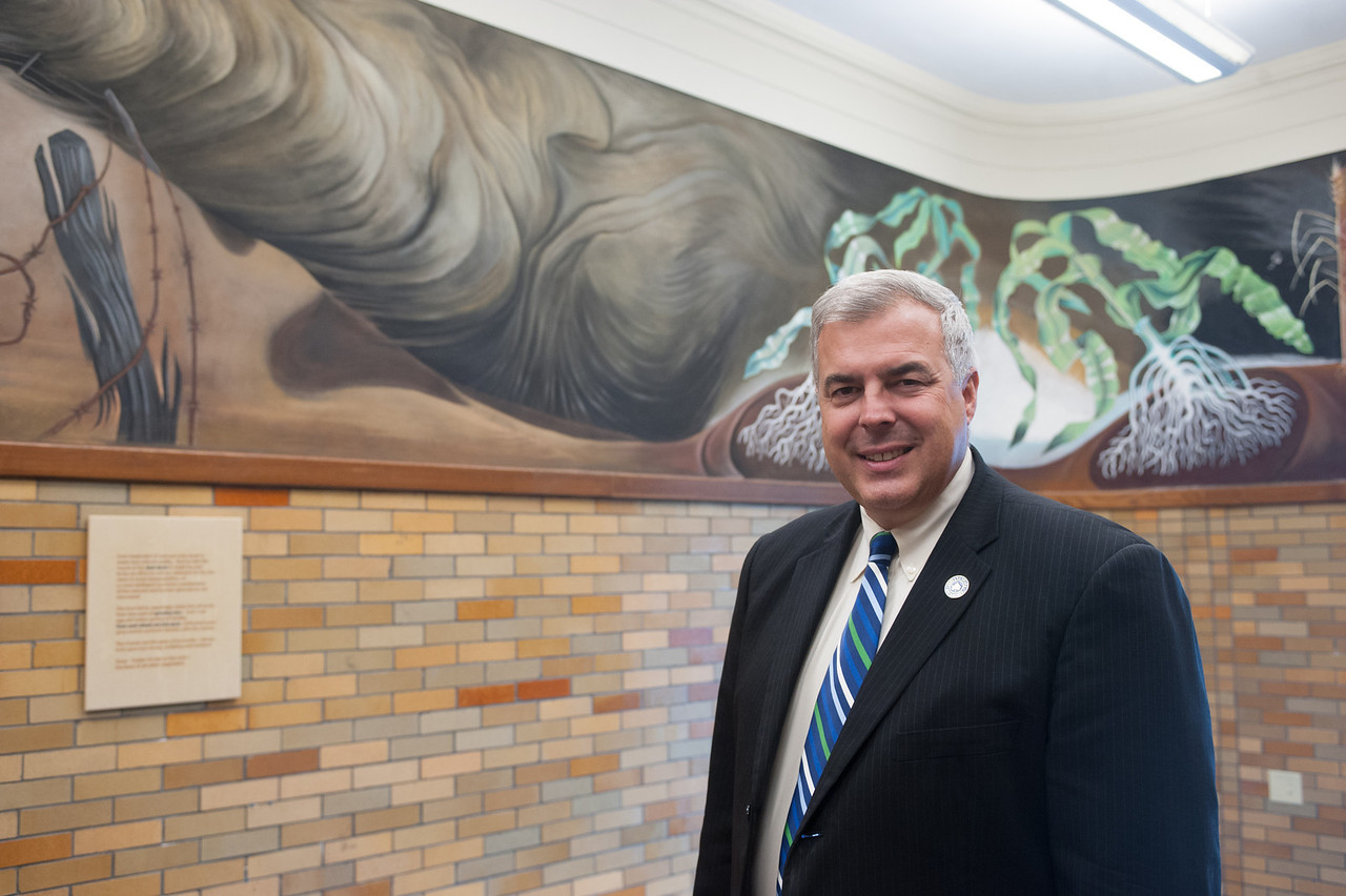 Brad Balch poses in front of the WPA mural in University Hall