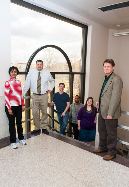 Tom Steiger poses with students and faculty in stairwell of Dreiser Hall