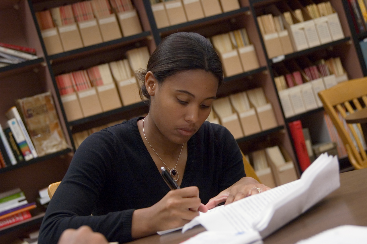 African American girl in black V nech with long sleeves, writing.Library shelves behind her.