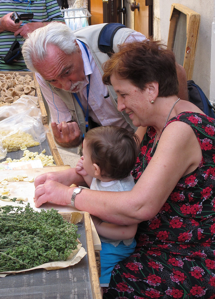 A demonstration of pasta making in Lecce.   The gent standing is our tour manager, Luigi, and the lady holding her grandchild talking to Luigi apparently appeared in a tv programme shown in the UK featuring Italian chef  Gino D'Acampo.