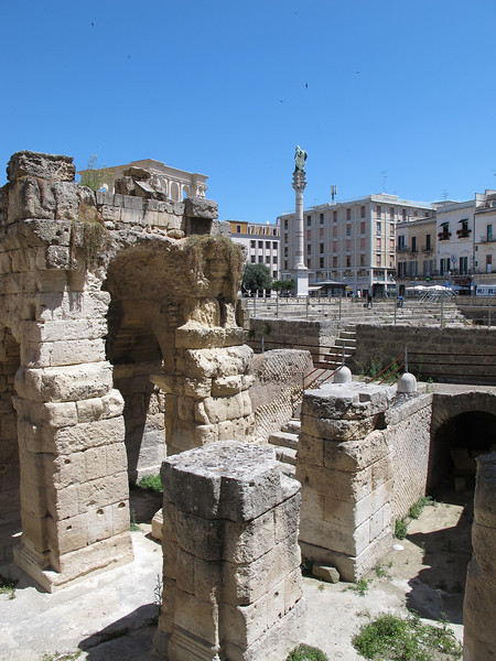 A modern piazza now sits over the remains of a Roman amphitheatre, remains of which are still visible here.