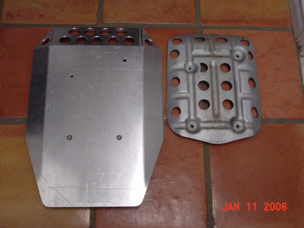 Notice the difference in size between the 2HE skidplate on the left and the factory skidplate on the right. New 2HE skidplates now come with the mounting hole contact points dimpled