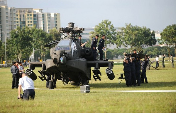 A Republic of Singapore Air Force Apache AH-64 helicopter sits on a field as its tail (R) is carried by air force engineers after it crashed-landed in Singapore on September 30, 2010.  The Apache helicopter crash-landed at an open field within a residential district on September 30, afternoon but no one was injured in the incident, the defence ministry said.  The Apache AH-64, built by US aviation giant Boeing, is a four-blade, twin-engine attack helicopter, and is used by the US, Israeli and Japanese militaries, among others.          AFP PHOTO/ROSLAN RAHMAN (Photo credit should read ROSLAN RAHMAN/AFP/Getty Images)