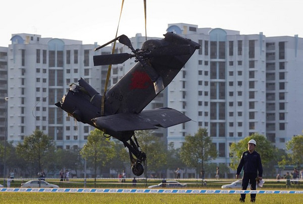 A member of the recovery crew watches as the tail section of a Republic of Singapore Air Force (RSAF) AH-64 Apache helicopter is lifted by a crane after it crash landed in the Woodlands area in northern Singapore September 30, 2010. Singapore's Ministry of Defence said the helicopter made a forced landing in the field, and the pilots appeared uninjured, local media reported.  REUTERS/Vivek Prakash (SINGAPORE - Tags: TRANSPORT MILITARY DISASTER)