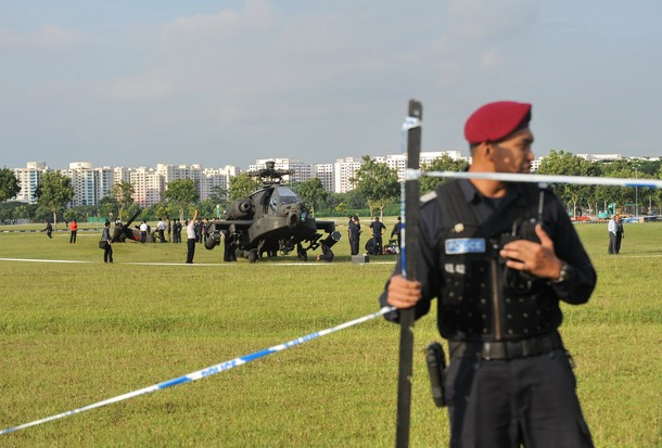 A police officer from the Singapore's Special Operation Command unit cordon off the area where an Apache helicopter crashed-landed in a field in Singapore on September 30, 2010. An Apache helicopter from Singapore's air force crash-landed at an open field within a residential district on September 30, but no one was injured in the incident, the defence ministry said. AFP PHOTO/ROSLAN RAHMAN (Photo credit should read ROSLAN RAHMAN/AFP/Getty Images)