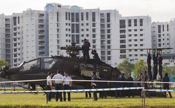 Military personnel detach the blades of a Republic of Singapore Air Force (RSAF) AH-64 Apache helicopter as it sits in an open field after crash landing in the Woodlands area in northern Singapore September 30, 2010. Singapore's Ministry of Defence said the helicopter made a forced landing in the field, and the pilots appeared uninjured, local media reported. REUTERS/Vivek Prakash (SINGAPORE - Tags: TRANSPORT MILITARY DISASTER)