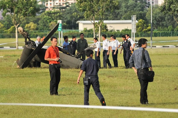 The tail of a Republic of Singapore Air Force Apache AH-64 helicopter sits on a field after it crashed-landed in Singapore on September 30, 2010.  The Apache helicopter crash-landed at an open field within a residential district on September 30, afternoon but no one was injured in the incident, the defence ministry said.  The Apache AH-64, built by US aviation giant Boeing, is a four-blade, twin-engine attack helicopter, and is used by the US, Israeli and Japanese militaries, among others.          AFP PHOTO/ROSLAN RAHMAN (Photo credit should read ROSLAN RAHMAN/AFP/Getty Images)