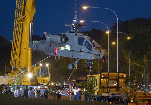 Members of a recovery crew supervise as the body of a Republic of Singapore Airforce (RSAF) Apache AH-64 helicopter is lifted by a crane after it crash-landed in the Woodlands area in northern Singapore September 30, 2010. Singapore's Ministry of Defence said the helicopter made a forced landing on the field, and the pilots appeared uninjured, local media reported.  REUTERS/Vivek Prakash (SINGAPORE - Tags: TRANSPORT MILITARY DISASTER)
