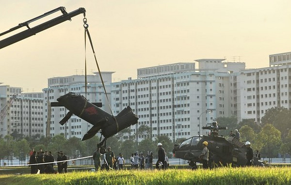 The broken tail section of a Republic of Singapore Air Force Apache AH-64 helicopter is lifted away after the helicopter was crash-landed in Singapore on September 30, 2010. The Apache helicopter crash-landed at an open field within a residential district on September 30 but no one was injured in the incident, the defence ministry said. The Apache AH-64, built by US aviation giant Boeing, is a four-blade, twin-engine attack helicopter, and is used by the US, Israeli and Japanese militaries, among others. AFP PHOTO/ROSLAN RAHMAN (Photo credit should read ROSLAN RAHMAN/AFP/Getty Images)