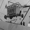 New Zealand Expedition 1948, June through August. Mobile 4-Yagi Antenna unit being loaded on a ship in Sydney bound for New Zealand.   In order to increase the accuracy of the observations made of discrete radio sources at the Dover Heights Field Station, observations of the same sources were planned for sites in Piha and Leigh in New Zealand, North Island.  These sites were almost three times higher in elevation (300 m) than the Dover site and allowed the rising and setting of the radio sources above the horizon to be measured with much greater accuracy.  This was critical in determining accurate celestial coordinates so that these radio source could be identified with objects known to astronomers using conventional optical telescopes.