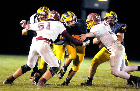 Don Knight/The Herald Bulletin<br /> Shenandoah's Lane Young runs between Scecina's Nate Canterbury (51) and Jordan Brown (31) during the sectional championship on Friday.