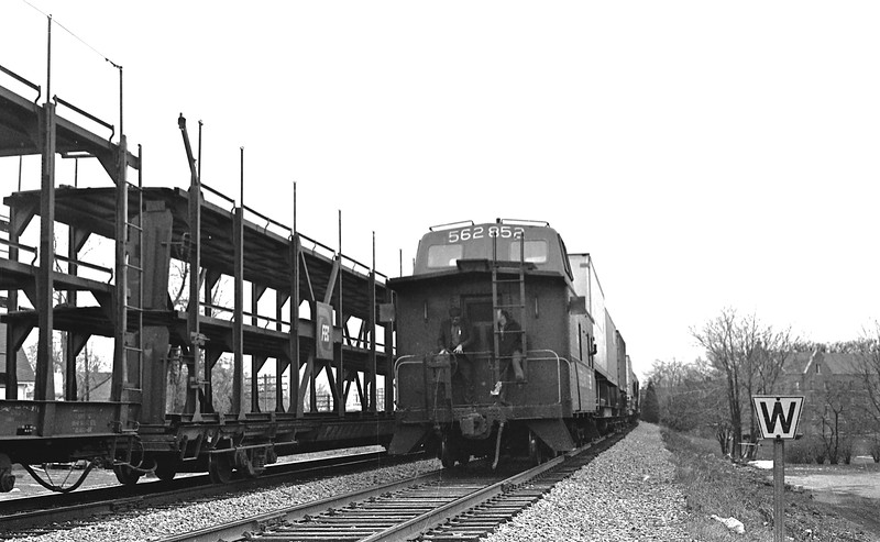 N&W Caboose #562852 is passing the campus of Millikin University at Decatur, IL.  The Conductor and Brakeman are shown riding on the rear platform of the caboose.<br /> (Photo by William A. Shaffer)