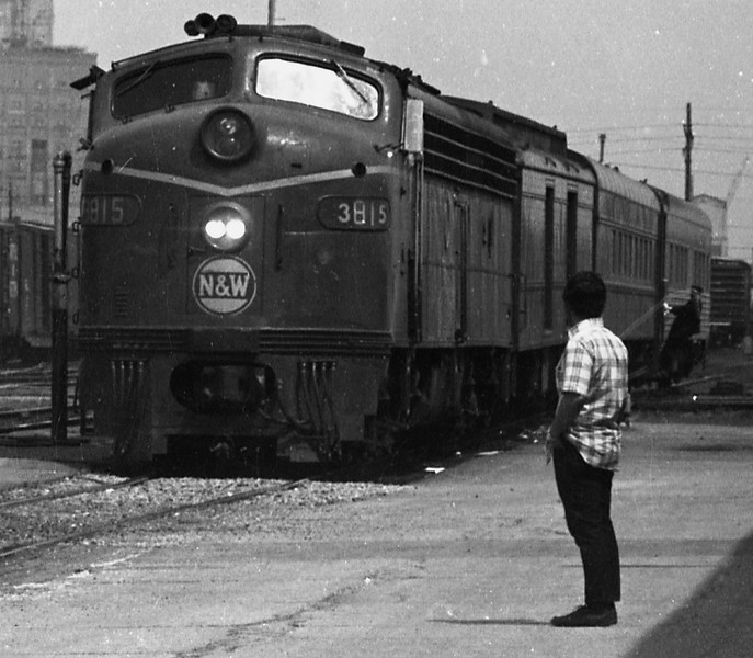 """N&W #3815 is shown arriving with #301, the southbound """"Wabash Cannon Ball"""".  They have just crossed the Illinois Central track at Wabic Tower and the Conductor is preparing to detrain while the train is still in motion.<br /> (Photo by William A. Shaffer)"""