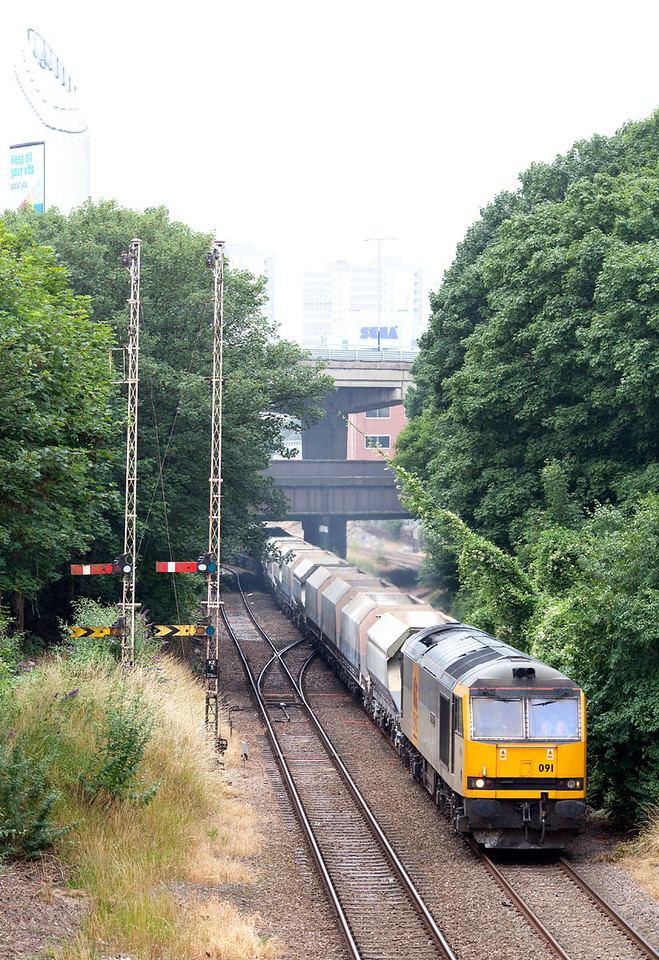 In Summer Drizzle, 60091 passes the semaphore signals at Kew East Junction with 6M34 11.23 Crawley-Peak Forest empty stone train. 11.7.09