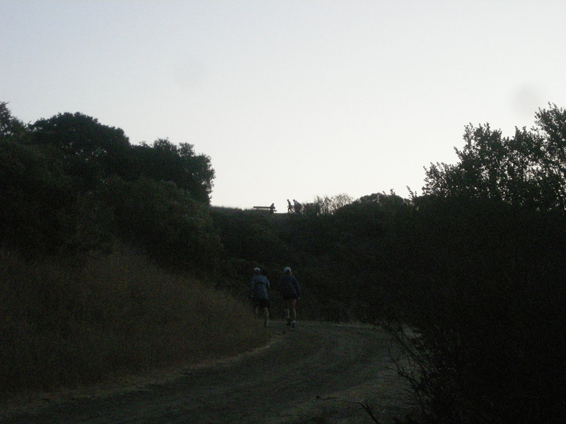 Donn (L) and Bonnelle disappearing round a corner. A couple of runners silhouetted next to the bench above Bonnelle's head.