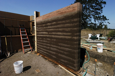 "This is what a completed wall looks like shortly after the formwork is removed. Over the course of about three days, the surface dries, and it will continue to cure through the coming months.  The top ""cap"" has a pressure treated two-by-six inlaid into it as a sill. The top cap is actually called 'Puddled Earth"" and contains proportionally more cement than the rammed earth mixture.  It goes on in  a slurry, and sets like cement."