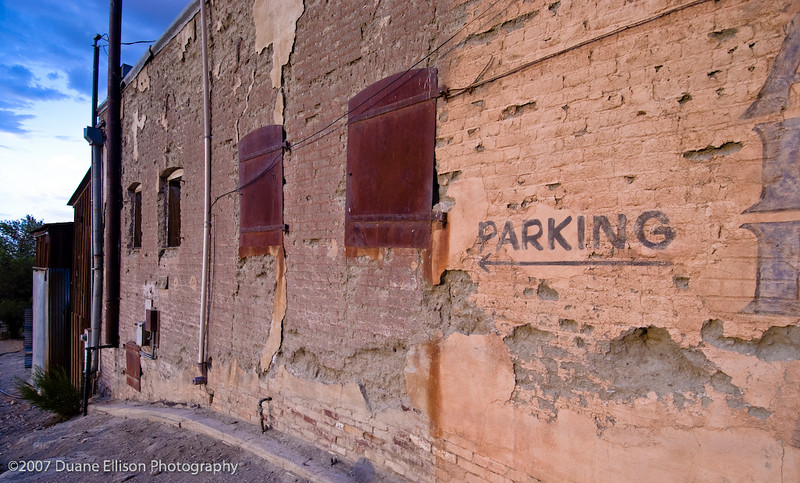 <b>Desert Shots-14</b><br>An old dilapidated building lit by the setting sun with parking painted on it