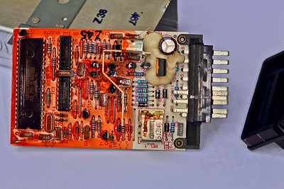 AMR1173 ECU - showing the full pc-board and the black plastic front cover on the right.