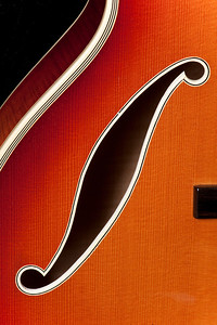 "A rare 1978 D'Aquisto New Yorker, 17-inch arch top guitar with brass strings.  Shown here is a sound hole on a spruce top with a subtle sunburst finish, the first such finish of its kind made by D'Aquisto.  Under 300 of this particular guitar were ever made, making it worth around 70 to $80,000 at current time.  D'Aquisto guitars were played by musicians such as Paul Simon and Joe Pass.  The owner of this guitar noted how D'Aquisto was a master at ""bringing out the sound,"" distinguishing it from other custom made guitars."