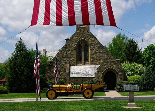 Mark Maynard   for The Herald Bulletin<br /> Parked in front the Anderson Memorial Park Cemetary chapel beneath a giant American flat erected by the Anderson Fire Department is an exact replica of the Marmon Wasp race car which Ray Harroun drive to victory in the first Indianapolis 500.