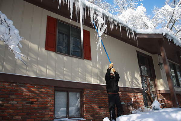 Jerry Landers knocking down icicles on January 6, 2014, after the big snowstorm.<br /> <br /> Photographer's Name: Rachel Landers<br /> Photographer's City and State: Anderson, Ind.
