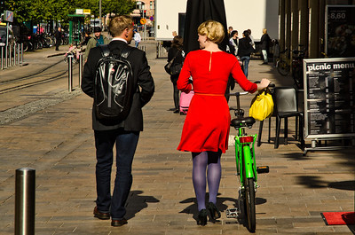 Blond girl with red dress, blue stockings, green bike and yellow purse walking with a guy in black, Helsinki, Finland