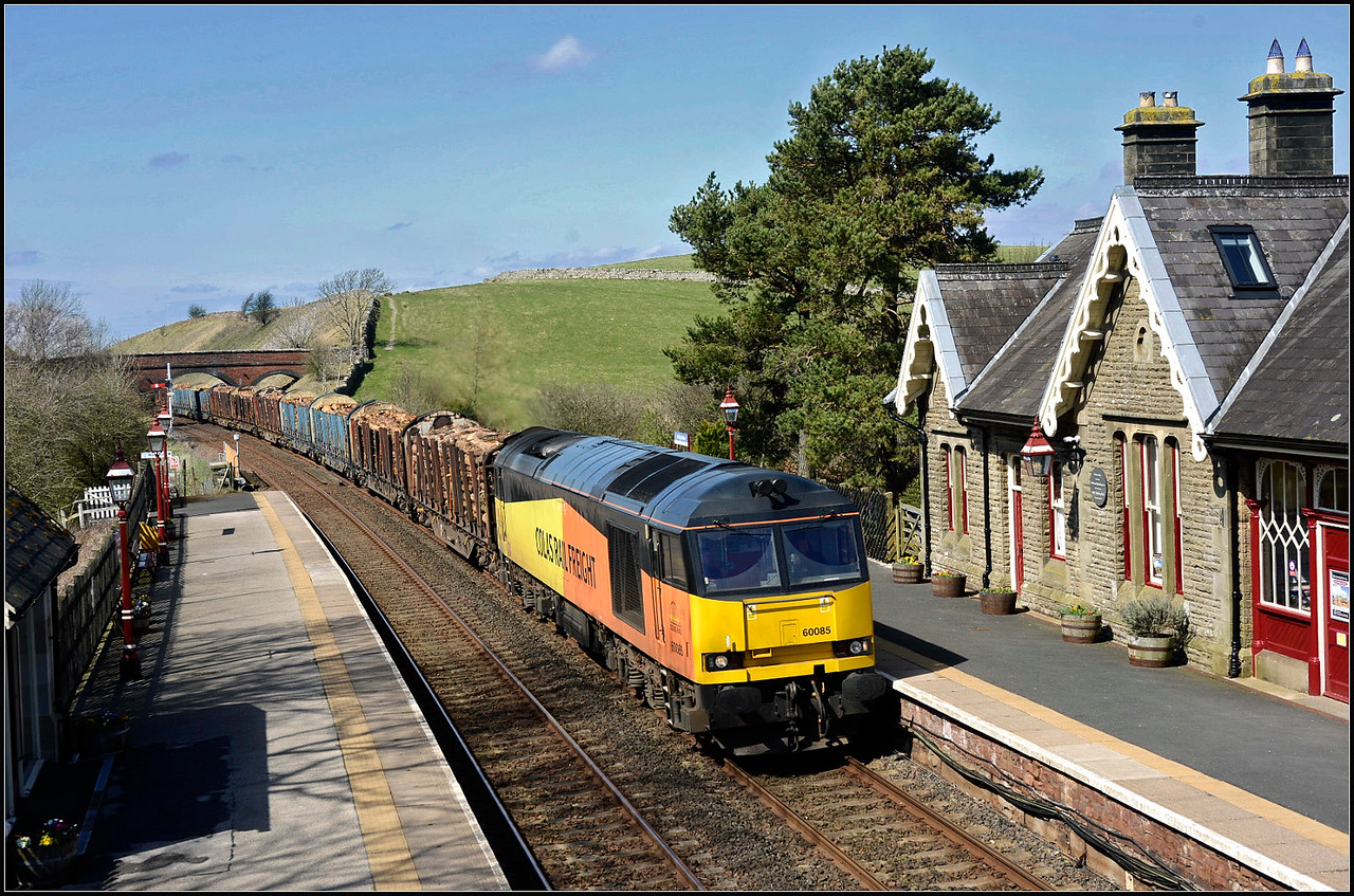 2018 04 19.60085 glides through Kirby Stephen station on 6J37 Carlisle-Chirk Kronospan  loaded timber working.