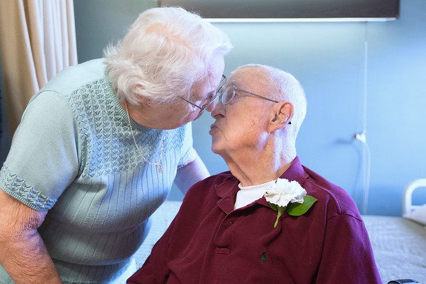 "Record-Eagle/Tessa Lighty <br /> Joyce Lundberg, left, bends down to give her husband, Andy Lundberg a kiss before their 70th wedding anniversary party at Tendercare Birchwood in Traverse City on Wednesday, September 13, 2017. Family and friends gathered at the nursing home to wish the two well. ""I didn't know the kids gave us so much credit,"" said Andy as he and his wife held back tears, listening to speaches from their children."
