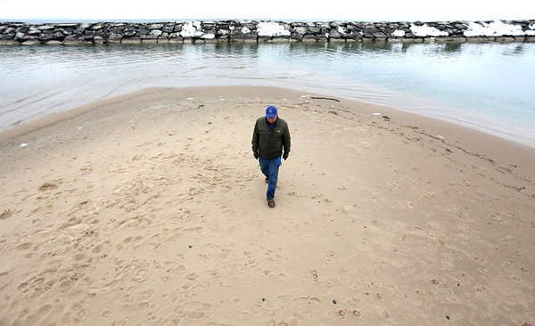 Record-Eagle/Tessa Lighty <br /> Harbormaster Russell Dzuba walks on a sand bar, which is normally deep enough for boats to easily pass through, at the entrance to the Leland harbor in Leland, Michigan on Tuesday, January 3, 2017. An ongoing fundraiser looks to secure $200,000 to go toward the purchase of a dredge vessel to dredge the Leland Harbor. If the harbor is not dredged this year, Dzuba said it will likely be closed for the 2017 boating season.