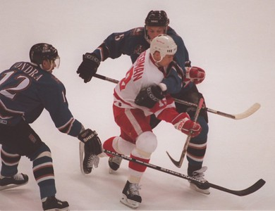 Detroit Red Wings Steve Yzerman (19) spits the two Washington Capitals defenders Peter Bondra (12) and Sergei Gonchar (55) during game 2 of the Stanley Cup game.
