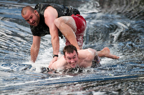2 guys enjoying the waterslide during Open Day, Castlewellan Holiday Week.
