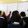 Girls writing about wishes for their phones during Coach Tumi SMS pilot research.  SKILLZ Street holiday programme, Soweto. July 2013.