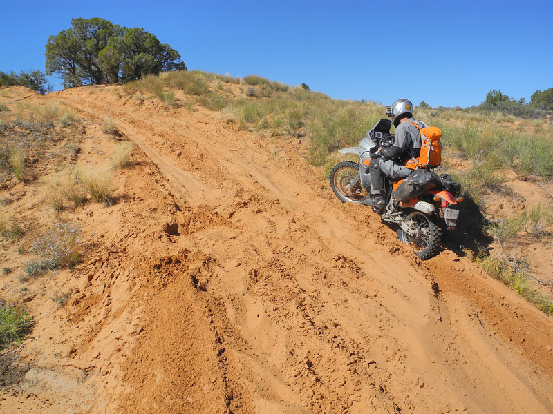 A rider struggles with deep sand on the Porcupine Rim Trail new Moab Utah.