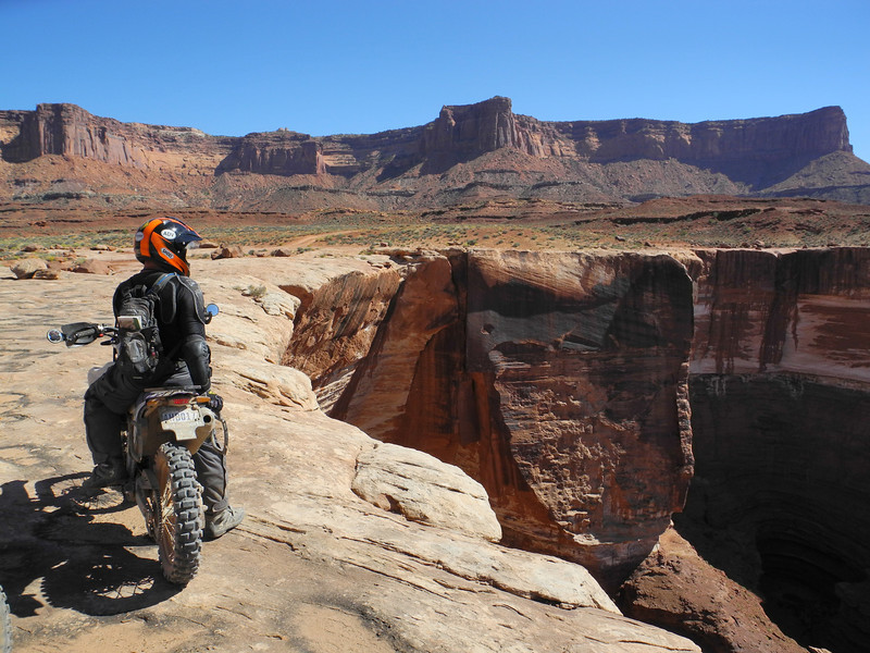 A rider dares to ride close to the edge of the White Rim Canyon in Canyonlands National Park, Utah